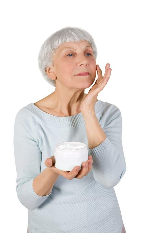 Mulher idosa encantador que aplica o creme cosmético em sua cara para cuidados com a pele faciais em um fundo branco imagens de stock