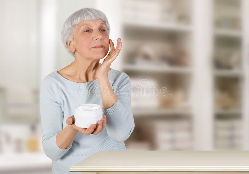 Mulher idosa encantador que aplica o creme cosmético em sua cara para cuidados com a pele faciais no banheiro em casa fotos de stock royalty free