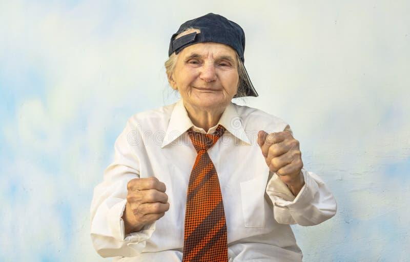 Mulher idosa engraçada que apoia algo imagem de stock