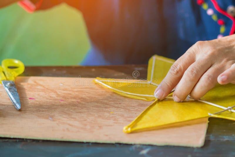 Mulher idosa fabricando e construindo pipa em forma de estrela ou nome tailandês Chula kite para venda no mercado local imagem de stock