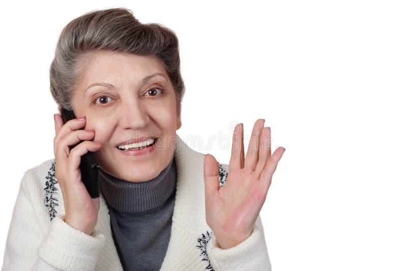 A mulher idosa fala no telefone imagem de stock