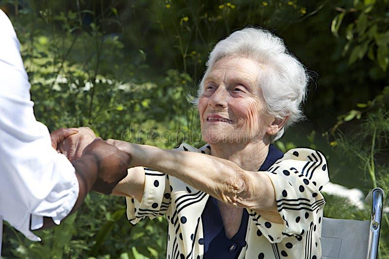 Mulher idosa feliz na cadeira de rodas imagem de stock