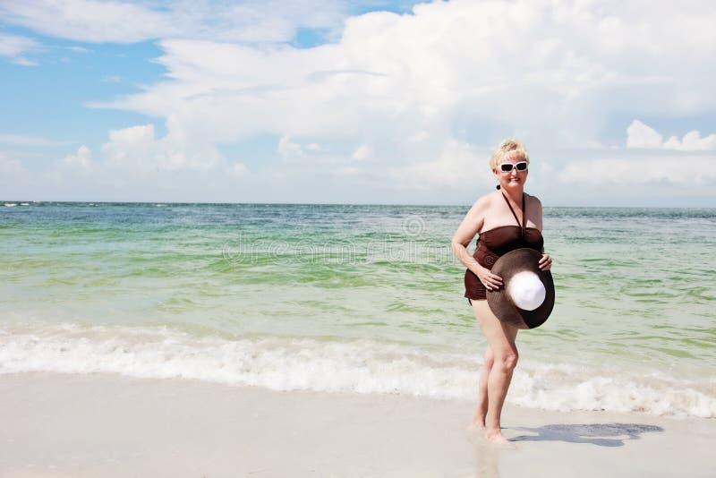 Mulher idosa feliz na praia fotografia de stock