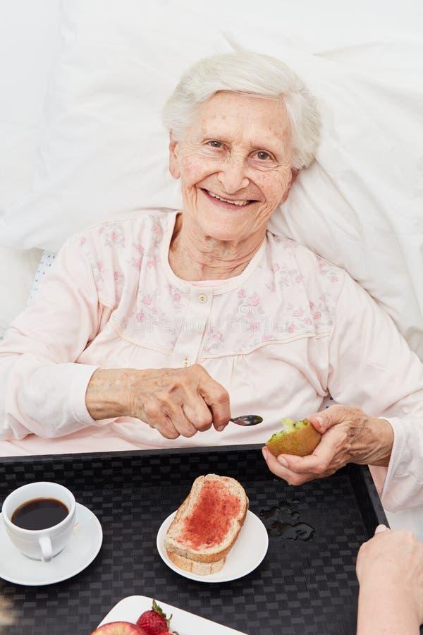 Mulher idosa feliz que come o caf? da manh? na cama fotografia de stock