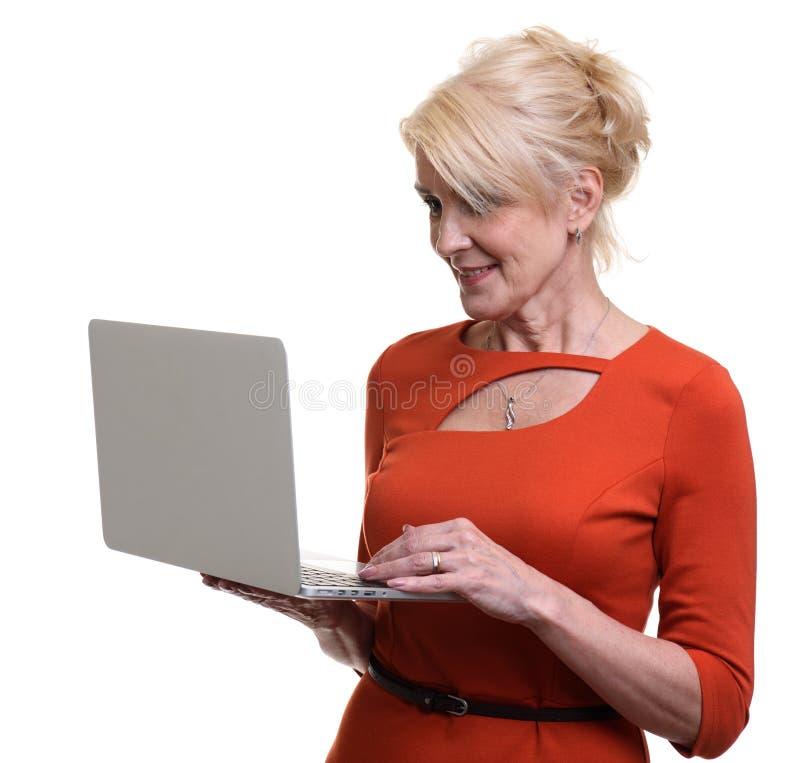 Mulher idosa feliz que usa o laptop imagem de stock royalty free