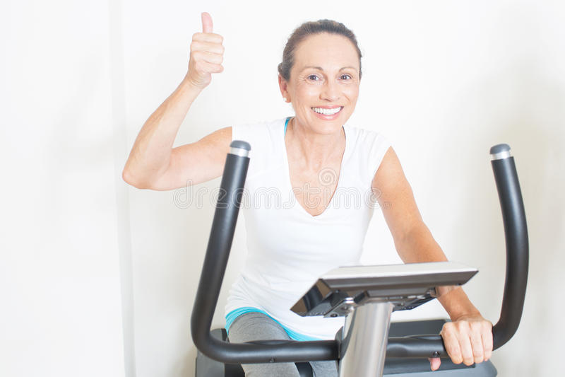 A mulher idosa gosta de dar um ciclo no gym fotos de stock royalty free