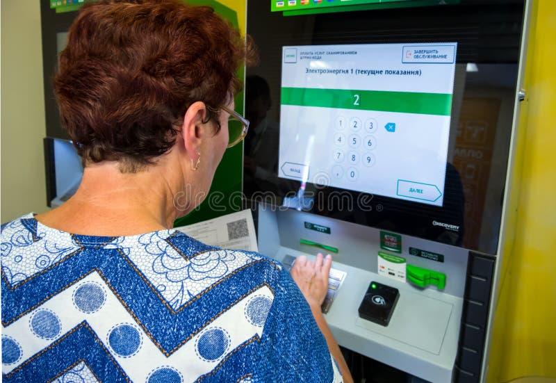 A mulher idosa incorpora leituras de medidor ao terminal do pagamento imagens de stock