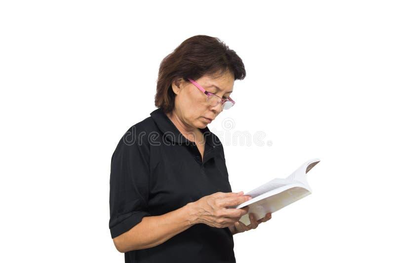 A mulher idosa lê o branco isolado livro no fundo imagens de stock royalty free