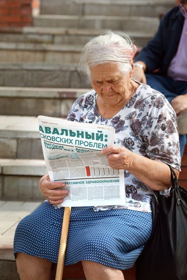 A mulher idosa lê o jornal a favor de Alexei Navalny