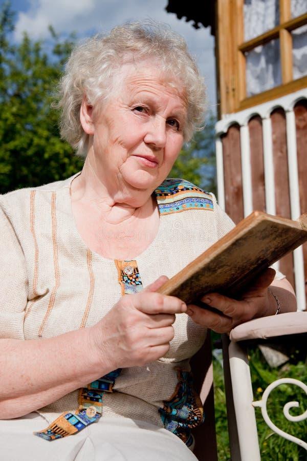 A mulher idosa lê um livro fotos de stock royalty free
