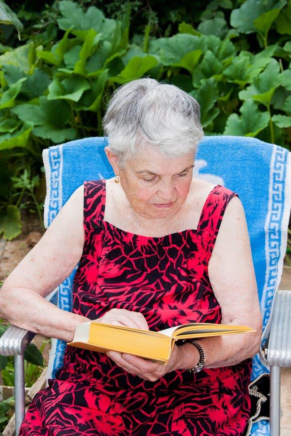 A mulher idosa lê um livro imagens de stock