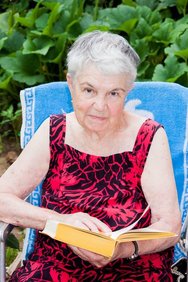 A mulher idosa lê um livro foto de stock