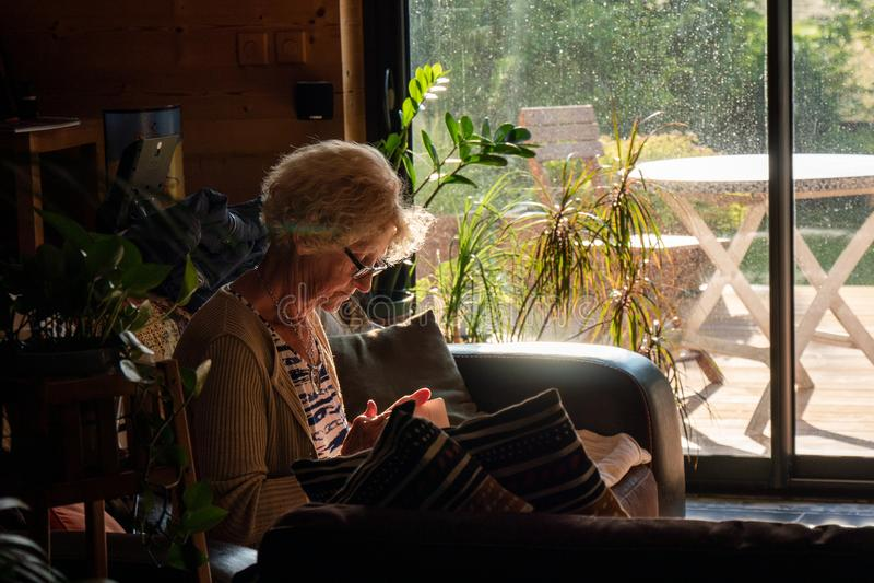 A mulher idosa lê um livro que senta-se no sofá foto de stock royalty free