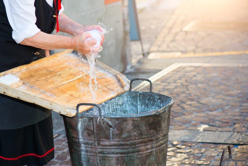 A mulher idosa lava a lavanderia com cubeta e placa de madeira como foto de stock