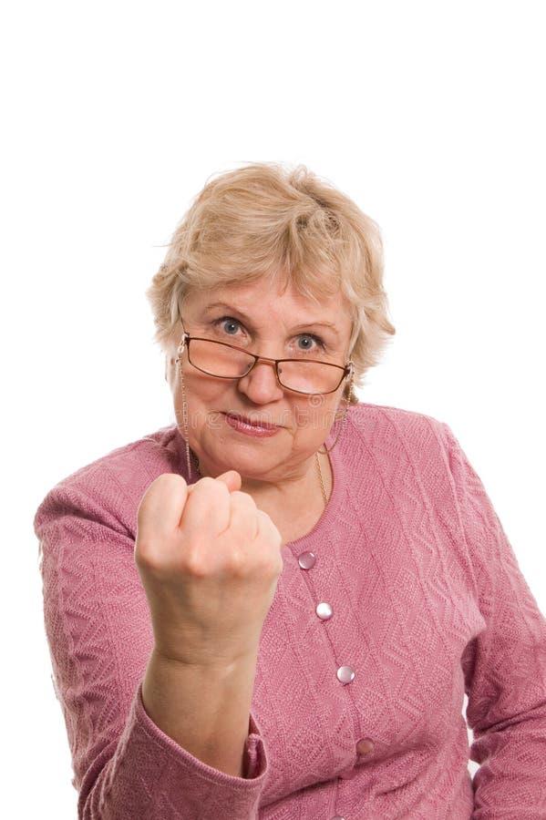 A mulher idosa mostra um punho fotos de stock royalty free