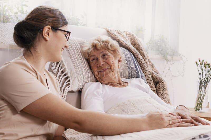 Mulher idosa na cama de hospital com o assistente social que ajuda a imagem de stock