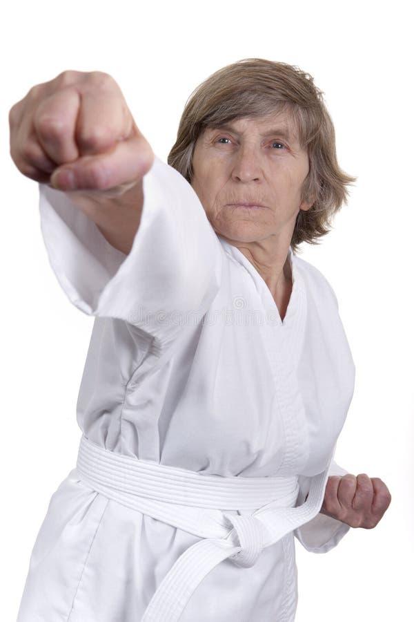 Mulher idosa na posição das artes marciais foto de stock