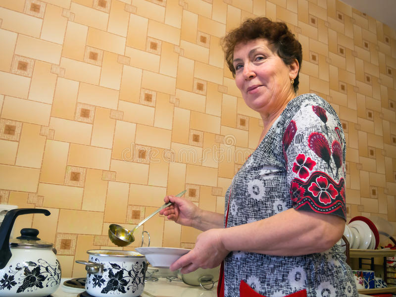 Mulher idosa na sopa de derramamento da cozinha em uma bacia fotos de stock