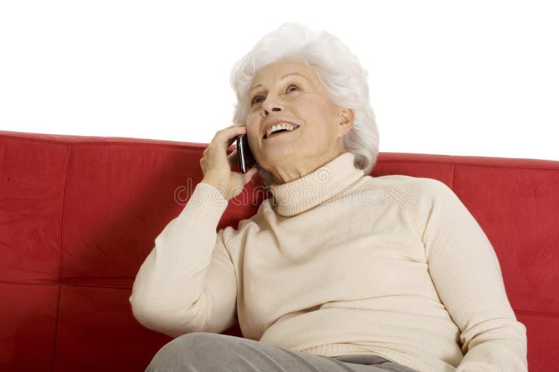 Mulher idosa no sofá com móbil fotos de stock