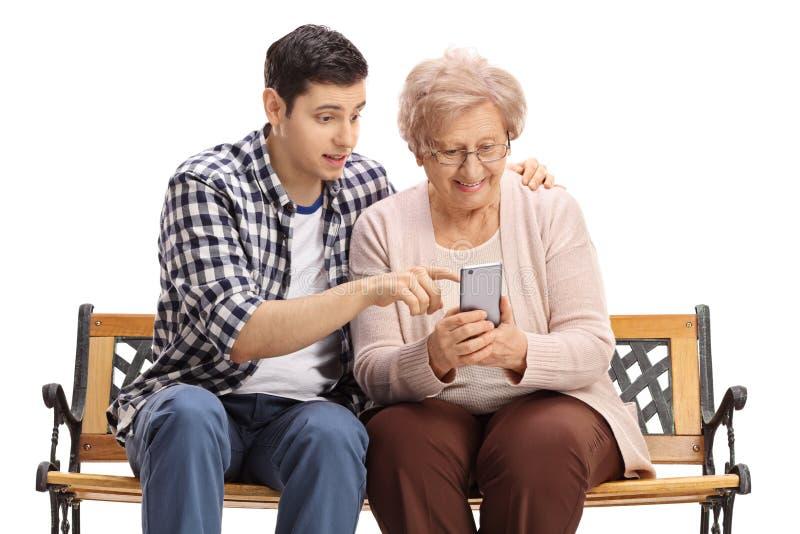 A mulher idosa nova do homem mostrando como usar o telefone celular fotos de stock