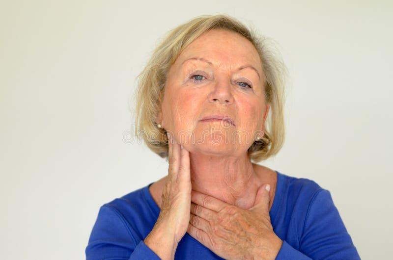 Mulher idosa pensativa com sua mão a seu pescoço fotografia de stock