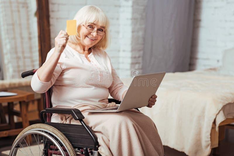 Mulher idosa positiva que usa o portátil fotografia de stock royalty free