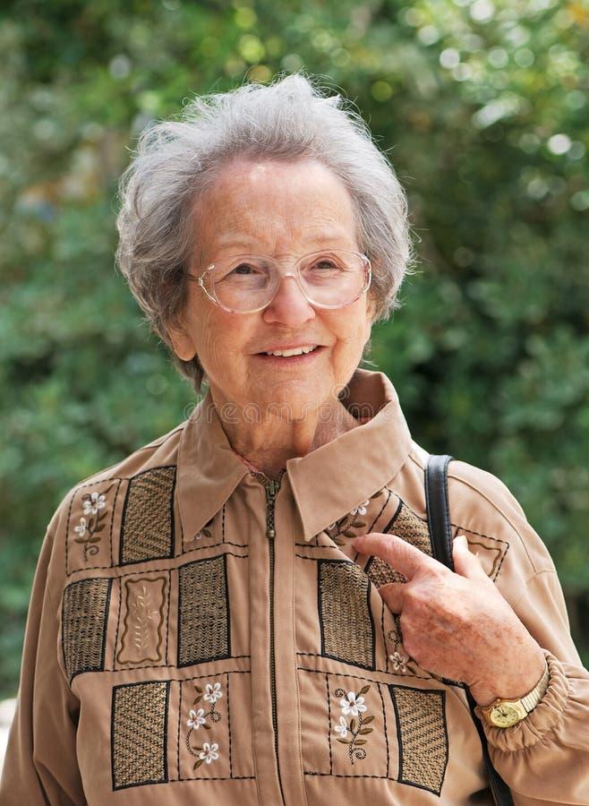 Mulher idosa que anda para fora no dia ensolarado imagens de stock royalty free