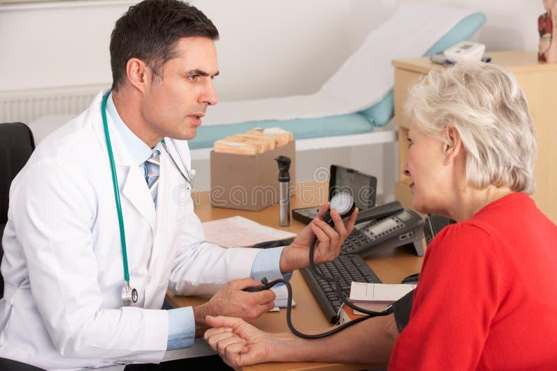Mulher idosa que começ lhe a pressão do sangue verific imagens de stock