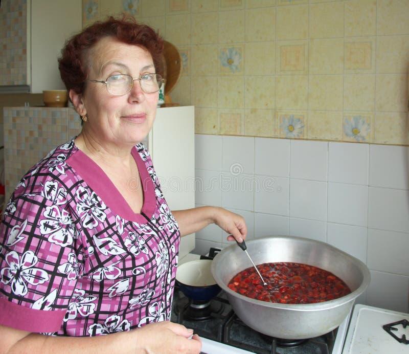 Mulher idosa que cozinha o doce de morango imagens de stock