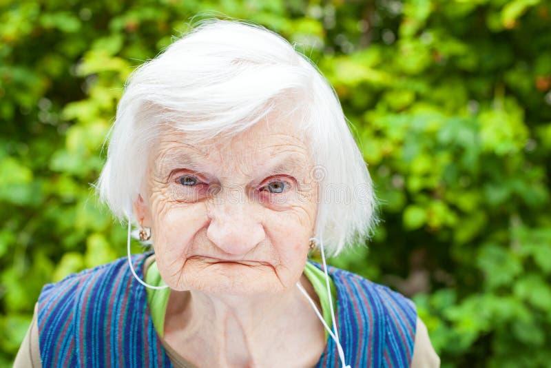 Mulher idosa que escuta a música com fones de ouvido imagens de stock