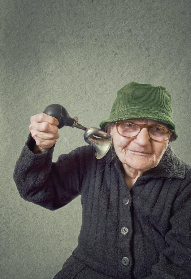 Mulher idosa que espreme o chifre em sua própria orelha. foto de stock royalty free