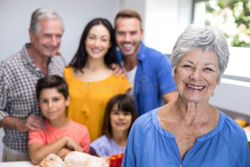 Mulher idosa que está na cozinha imagens de stock