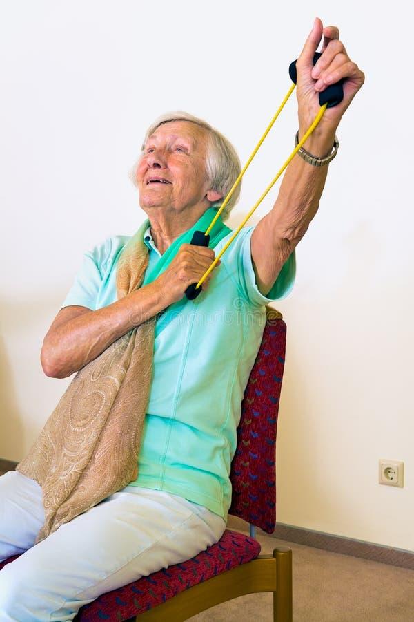Mulher idosa que exercita seus ombros fotos de stock