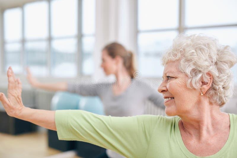 Mulher idosa que faz esticando o exercício na classe da ioga fotos de stock royalty free