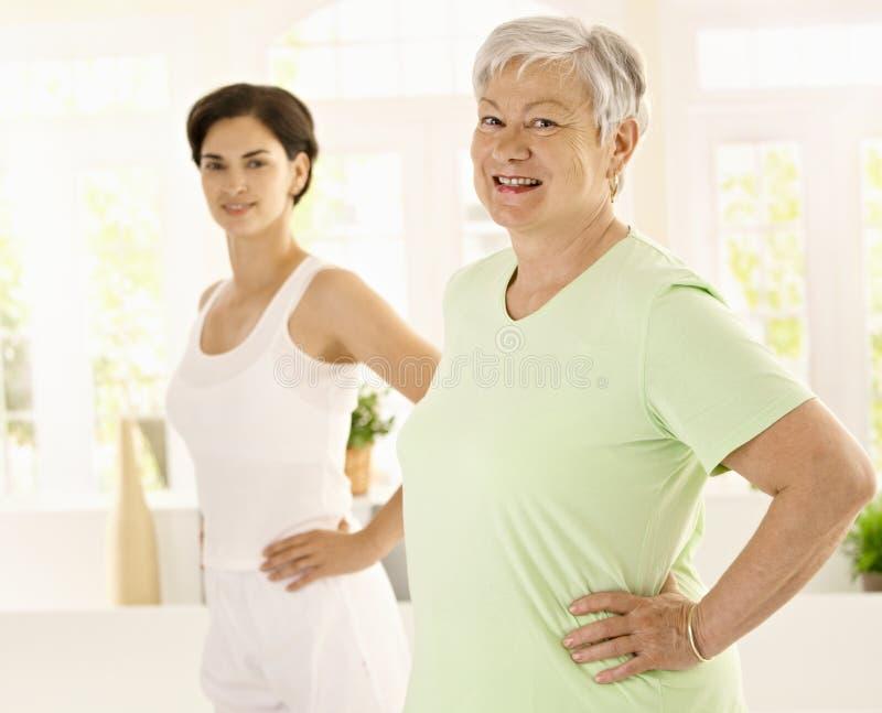 Mulher idosa que faz exercícios com instrutor fotografia de stock royalty free
