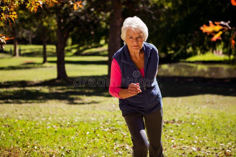 Mulher idosa que faz movimentar-se foto de stock