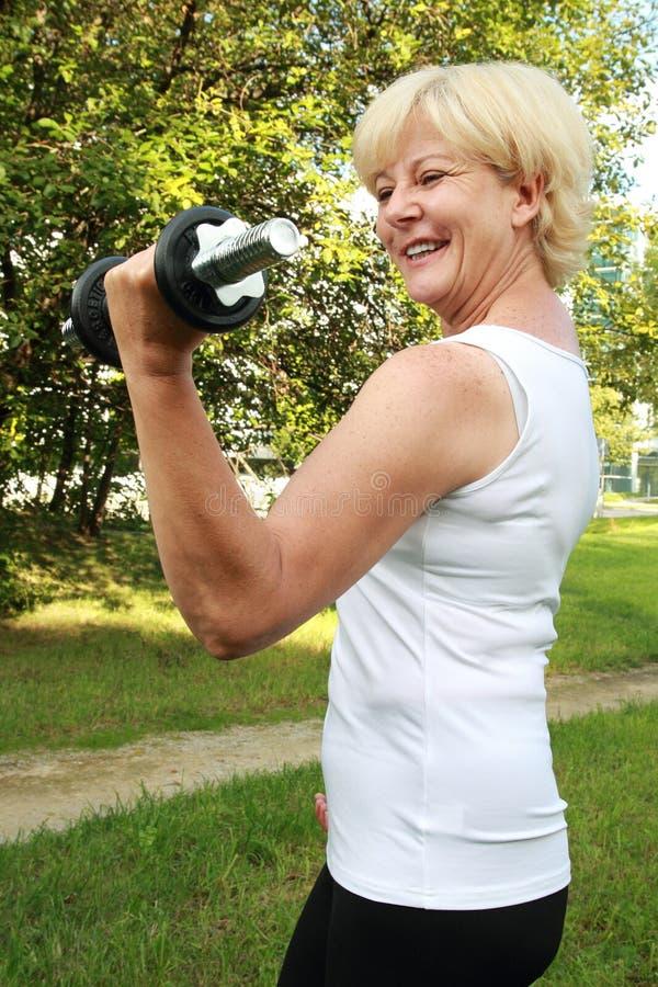 Mulher idosa que faz o treinamento exterior com peso imagem de stock royalty free