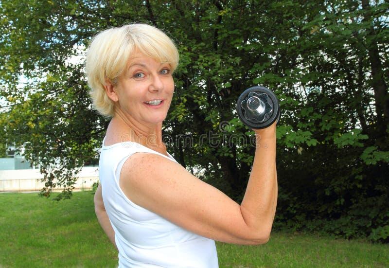 Mulher idosa que faz o treinamento exterior em um parque com peso fotos de stock royalty free