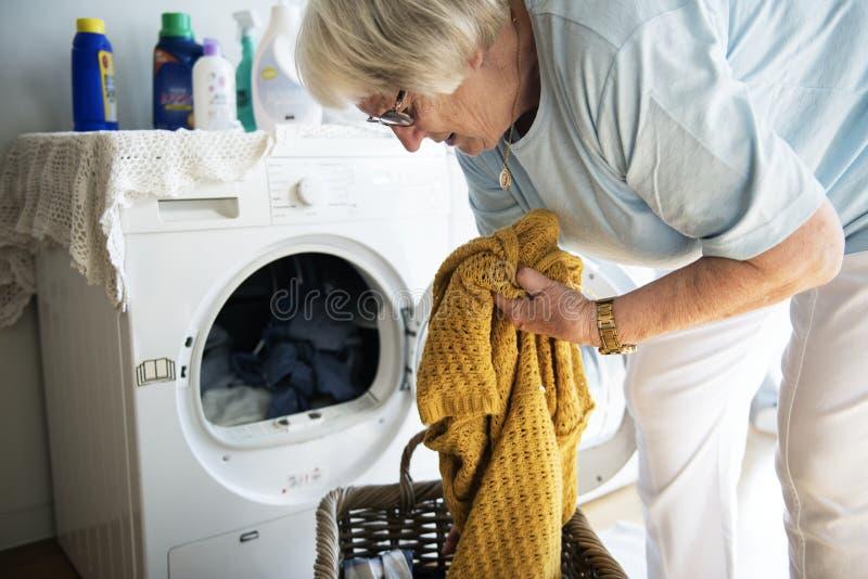 Mulher idosa que faz uma lavanderia imagem de stock