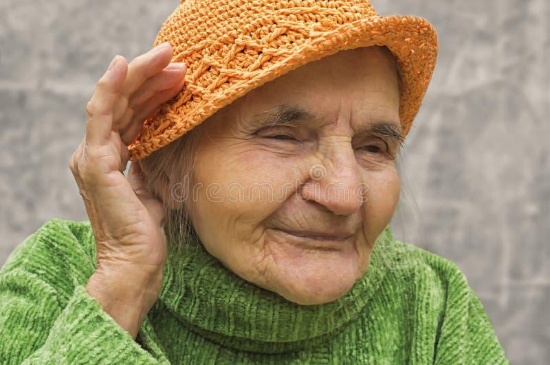 Mulher idosa que guarda a mão perto de uma orelha imagens de stock royalty free