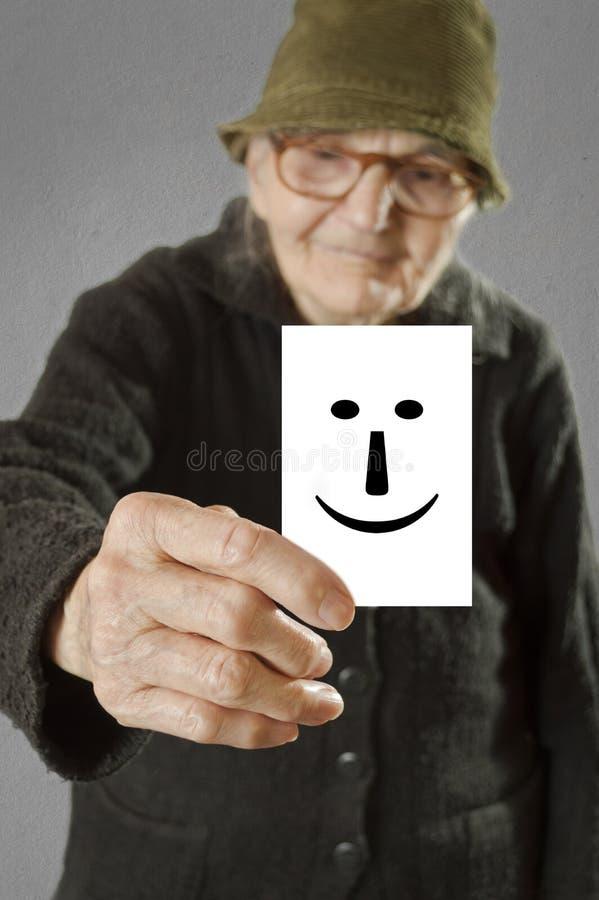 Mulher idosa que guarda o cartão com o emoticon feliz impresso. foto de stock