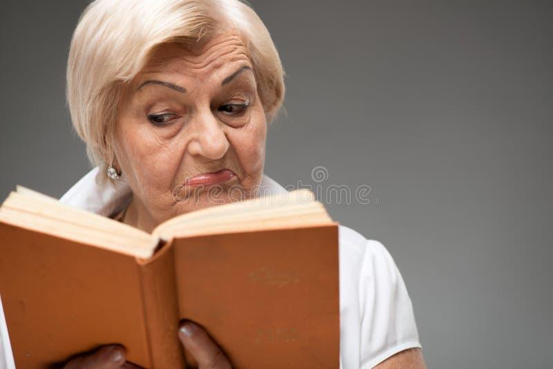 Mulher idosa que guarda o livro amarelo fotografia de stock