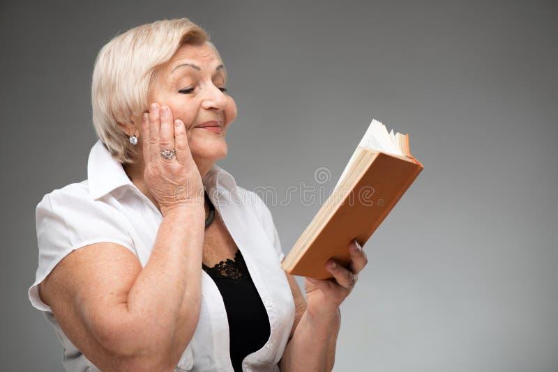 Mulher idosa que guarda o livro amarelo imagem de stock royalty free