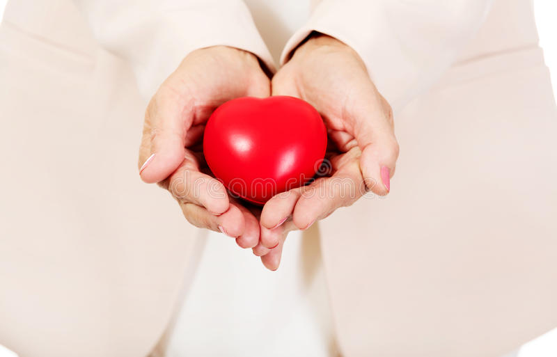 Mulher idosa que guarda o modelo do coração nas palmas abertas imagem de stock