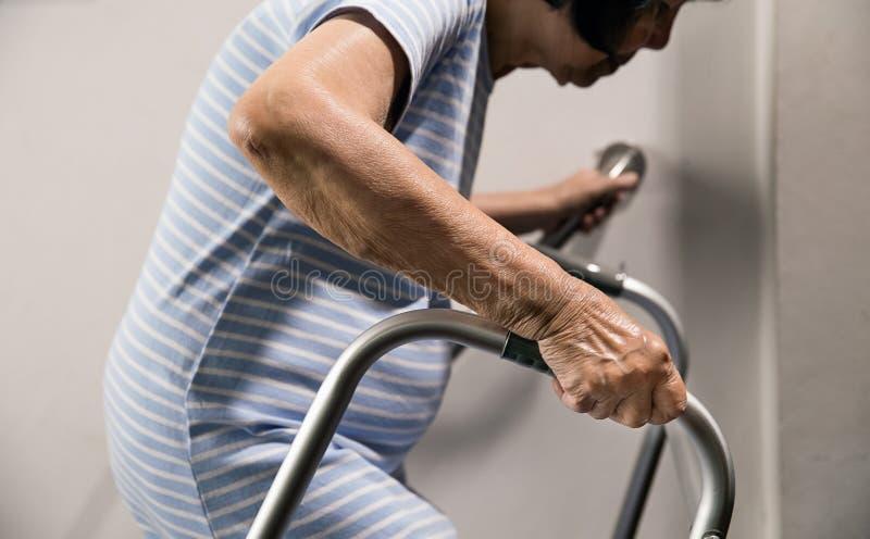 Mulher idosa que guarda sobre o corrimão e o caminhante para a segurança imagem de stock