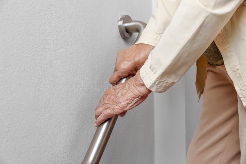A mulher idosa que guarda sobre o corrimão para a caminhada da segurança pisa fotografia de stock