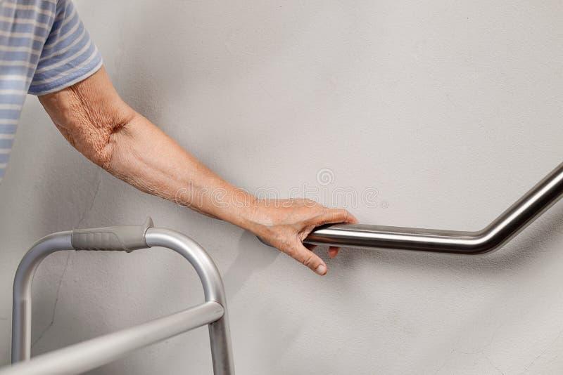 A mulher idosa que guarda sobre o corrimão para a segurança pisa imagem de stock