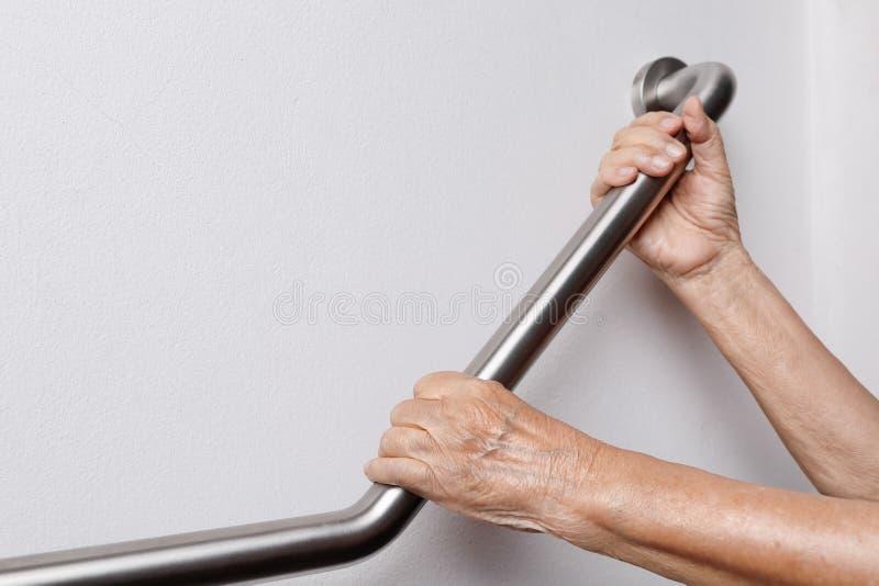 A mulher idosa que guarda sobre o corrimão para a segurança pisa foto de stock