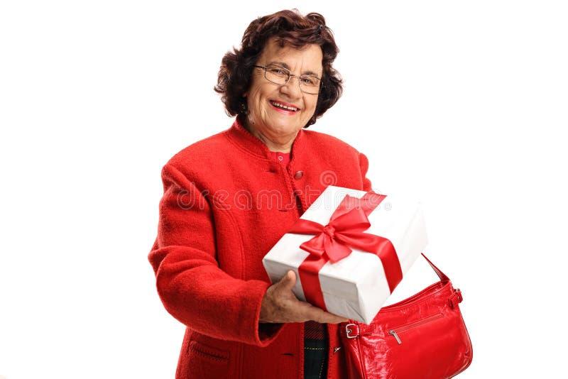 Mulher idosa que guarda um presente em uma caixa foto de stock