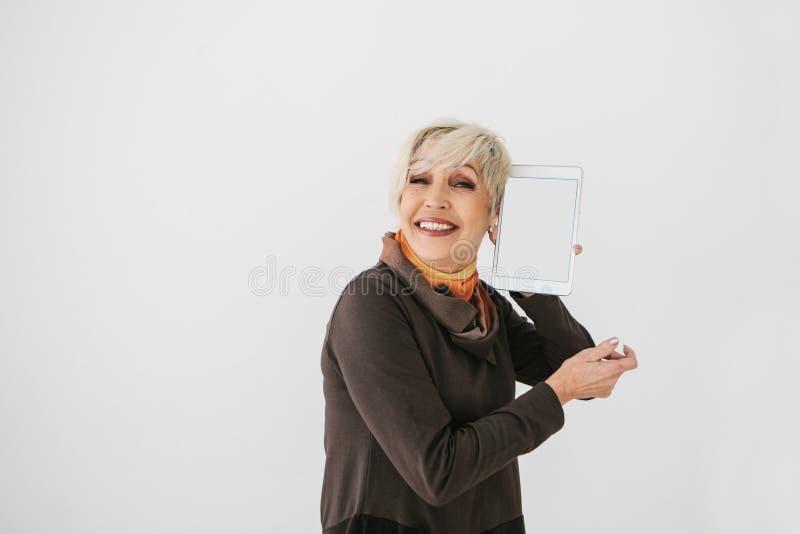 Mulher idosa que guarda uma tabuleta com uma tela e um sorriso brancos vazios A geração mais velha e a tecnologia moderna foto de stock